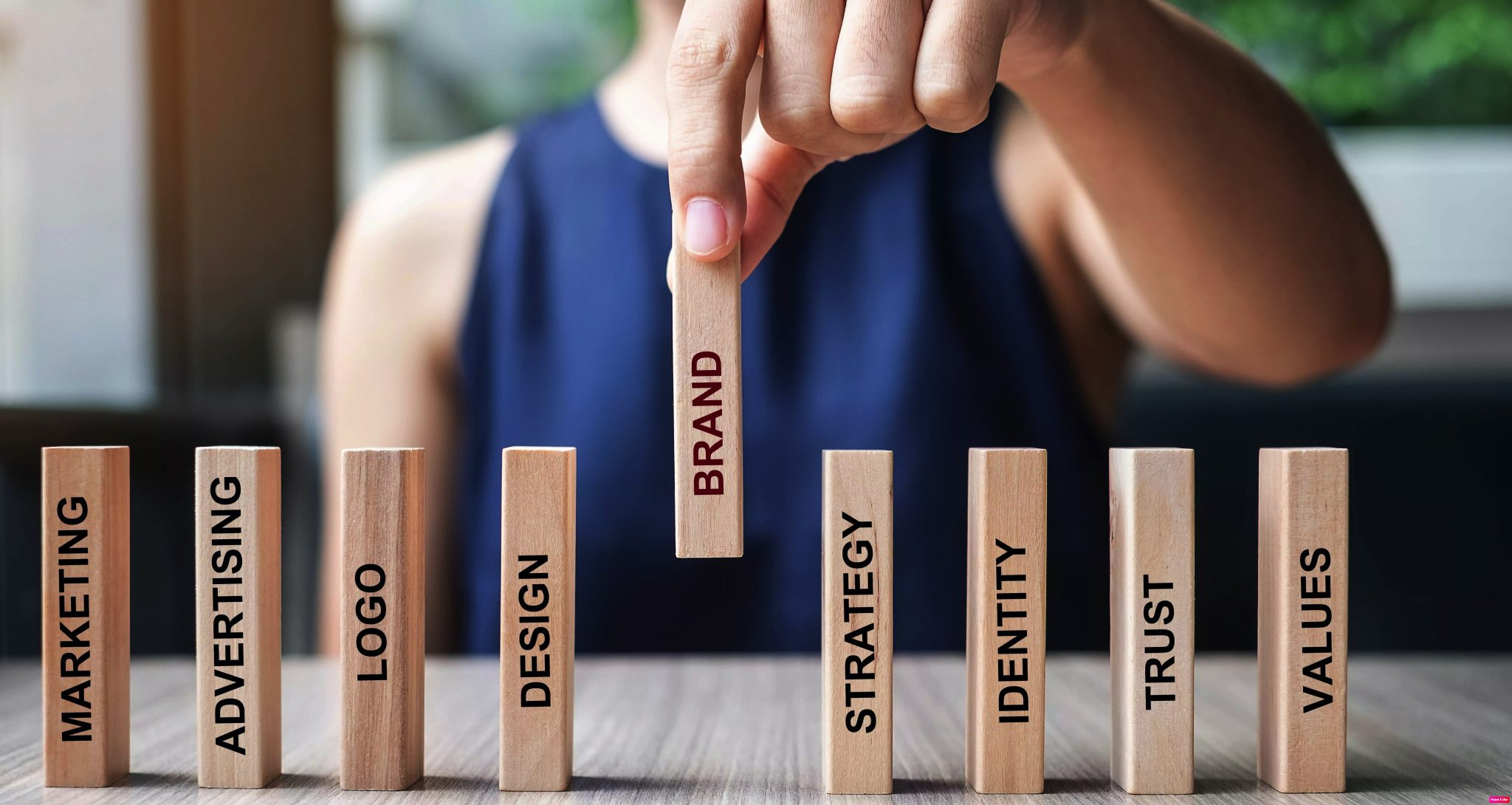 businesswoman2-hand-placing-or-pulling-wooden-dominoes-with-brand-text-and-marketing-advertising-logo_t20_YwXeLX
